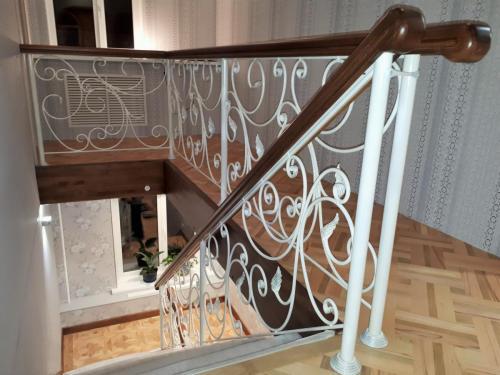 Лестница на металлокаркасе с кованым ограждением и деревянным поручнем